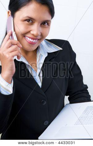 Businesswoman listening to ihr Handy halten Dokumente