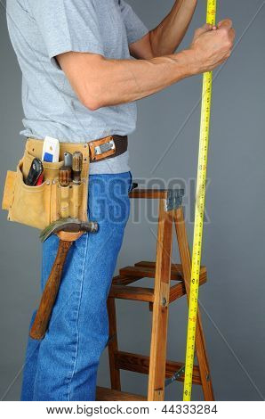 Closeup of a contractor standing on a wooden ladder holding a measuring tape. Vertical format over a gray background. Man is unrecognizable.