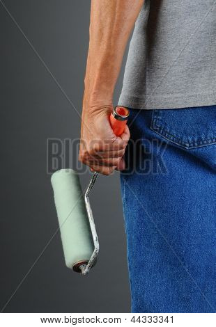 Closeup of a male painter seen from behind while he holds a paint roller by his side. Man is unrecognizable, torso and legs only. Vertical format.