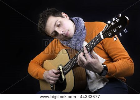 Man On Background Play On Guitar.