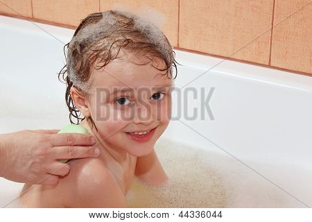 Mom's hands are washed with soap back the little blond boy in bathroom