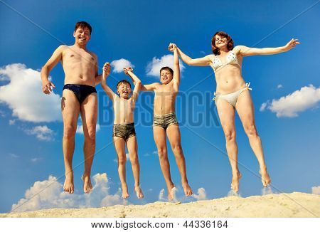 Photo of happy family jumping on sand during summer vacation