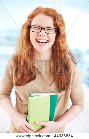 Teenage girl in eyeglasses holding books and laughing