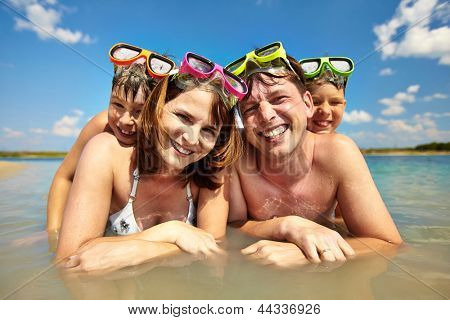 Photo of happy family of divers looking at camera during summer vacation