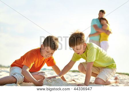 Photo of happy siblings playing on sand on summer vacation
