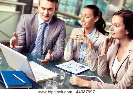 Portrait of business partners looking at laptop display at meeting, focus on pensive female