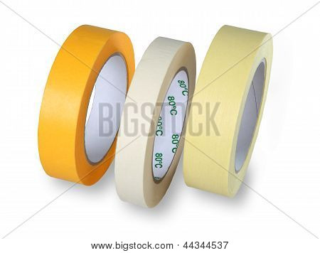 Three Rolls Of Narrow Paper Tape In White, Yellow And Brown, Isolated On White Background, With The