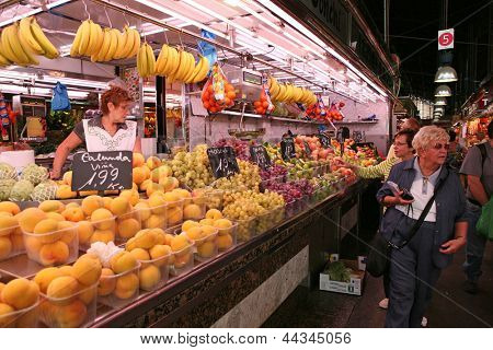 BARCELONA - OCTOBER, 2: Tourists in famous La Boqueria market on October 2, 2009 in Barcelona. One of the oldest markets in Europe that still exist. Established 1217.