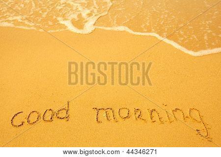 Good morning - written in sand on beach texture.