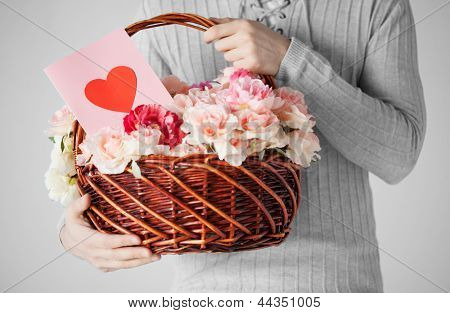 close up of man holding basket full of flowers and postcard.