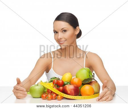 healthy woman with measuring tape and lots of fruits
