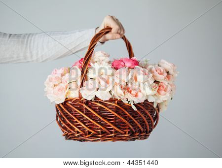 close up of man's hand holding basket full of flowers.