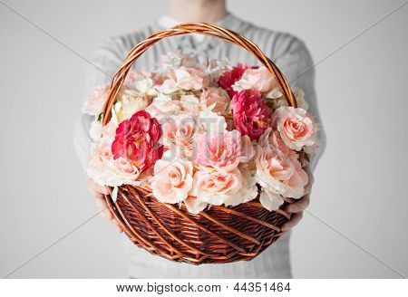 close up of man holding basket full of flowers.