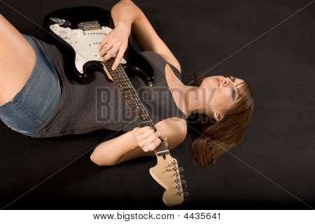 Teenage Girl With Rock Guitar Lying Down On Floor