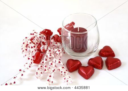 Ribbon, Unlit Candle And Chocolate Hearts.