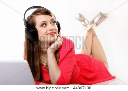 Cute Girl With Headphones And Laptop Lying