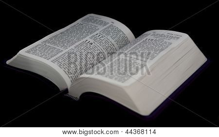 Open Bible To Psalm 118 Isolated On A Black Background.