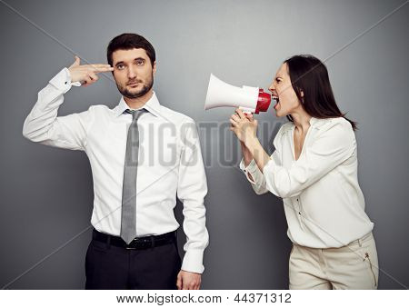 angry woman shouting at the tired man over dark background