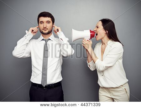 emotional woman shouting in megaphone at the calm man
