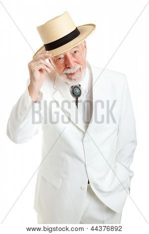 Handsome senior Southern gentleman in a white suit and string tie, tipping his straw hat politely.  Isolated on white.
