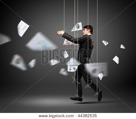 Image of businessman hanging on strings like marionette. Conceptual photography
