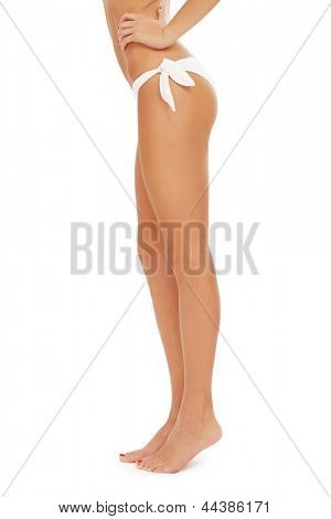 Long sexy legs of slim fit tanned woman over white background