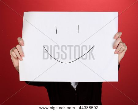 Woman holding paper with smile, on color background
