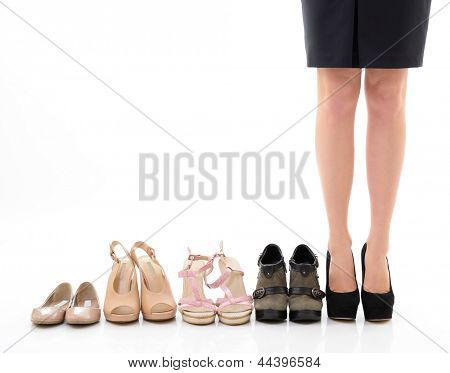 Shopping and sale. Female legs with shoes assortment, young woman put shoes on in shop and makes her choice, front view. Over white background
