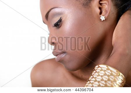Beautiful young african woman posing at studio in bijouterie, face with hand portrait over white background
