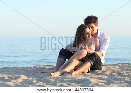 Casal abraçando sentado na areia da praia