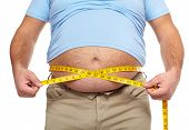 stock photo of body fat  - Fat man holding a measuring tape - JPG