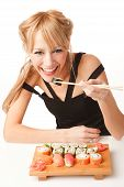Young Woman Eating Sushi With Chopsticks