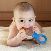 stock photo of teething baby  - Portrait of a cute 6 month old baby boy or girl playing with a teething toy - JPG