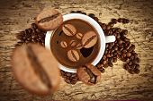 stock photo of negro  - Coffee cup with coffee beans on the wooden table - JPG