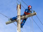 foto of electrician  - Electrician working at height without the aid of vehicles against the blue sky - JPG
