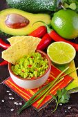 stock photo of nachos  - Fresh guacamole dip with nacho chips and ingredients - JPG