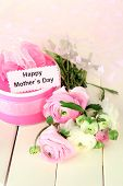 Ranunculus (persian buttercups) and gift for mothers day, on white wooden background