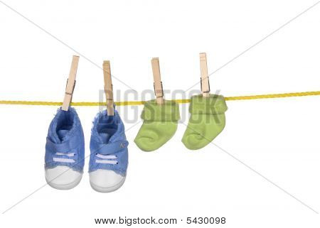 Baby Shoes And Socka Hanging On A Clothesline