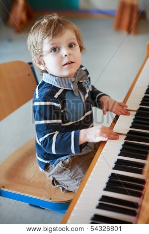 Little Toddler Boy Playing Piano At Music School.