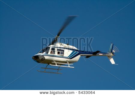 White Helicopter In Flight With Blue Sky Background