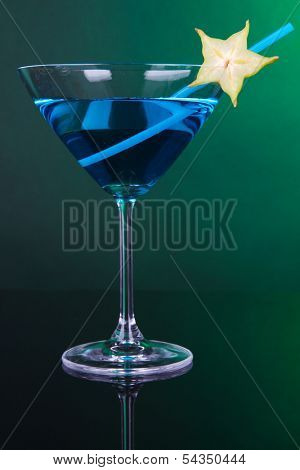 Blue cocktail in martini glass on dark green background