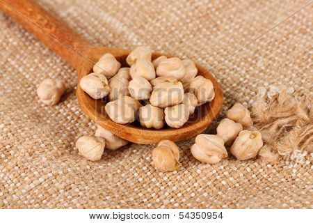 White chickpeas over wooden spoon on sackcloth background