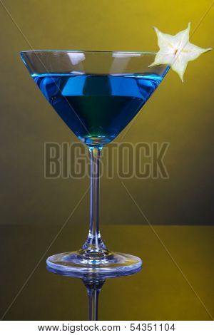 Blue cocktail in martini glass on dark yellow background