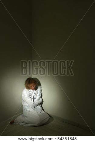 Mentally ill man in strait-jacket in room corner