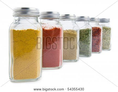 Set of assorted colorful powder spices in glass bottle isolated on white background
