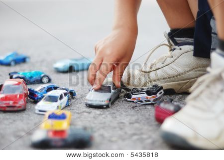 Kid Playing With Cars Toys