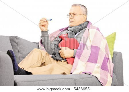 Sick mature man on a sofa with a hot-water bottle looking at thermometer isolated on white background