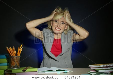 Irate teacher sitting at table on dark colorful background