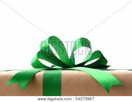 Closeup of a plain wrapped Christmas gift with green ribbon and bow. Only the top portion of the present is shown against a white background. Horizontal format.