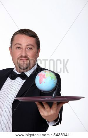puffy man dressed in waiter is holding a platter with a little globe on it